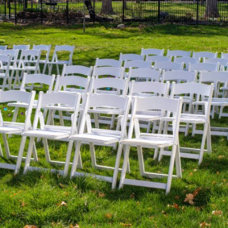 Rows of folding white chairs set up for a wedding on some green grass in a park.